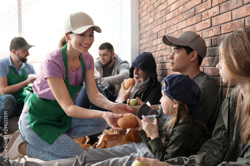 Volunteers giving food to poor people indoors Canvas Print