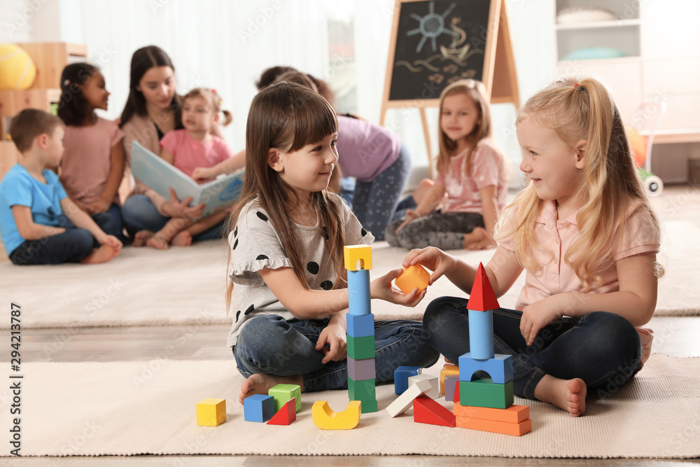 Fototapety, obrazy: Cute girls playing with building blocks on floor while kindergarten teacher reading book to other children indoors