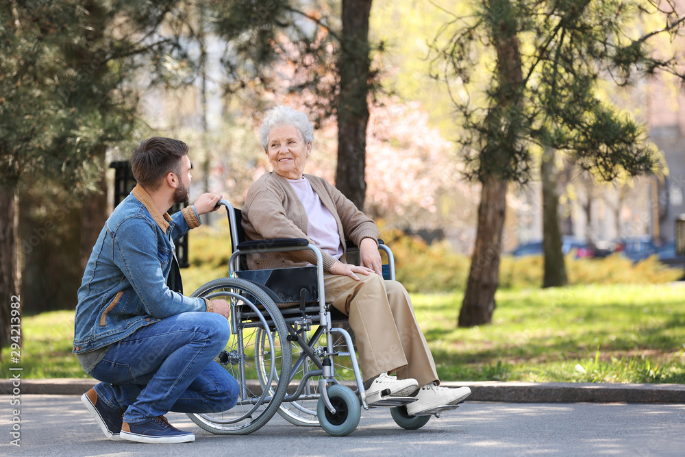 Fototapeta Senior woman in wheelchair with young man at park