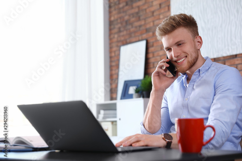 Fotomural  Young man talking on phone while using laptop at table indoors
