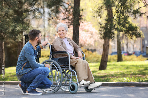 Fototapeta Senior woman in wheelchair with young man at park obraz