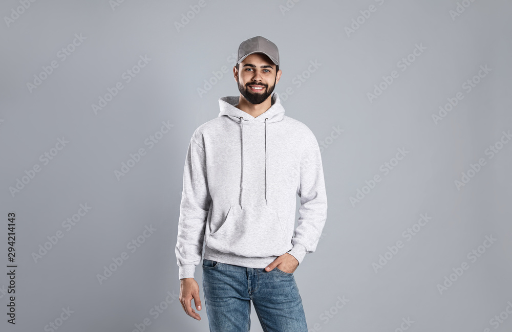 Fototapeta Portrait of young man in sweater on grey background. Mock up for design