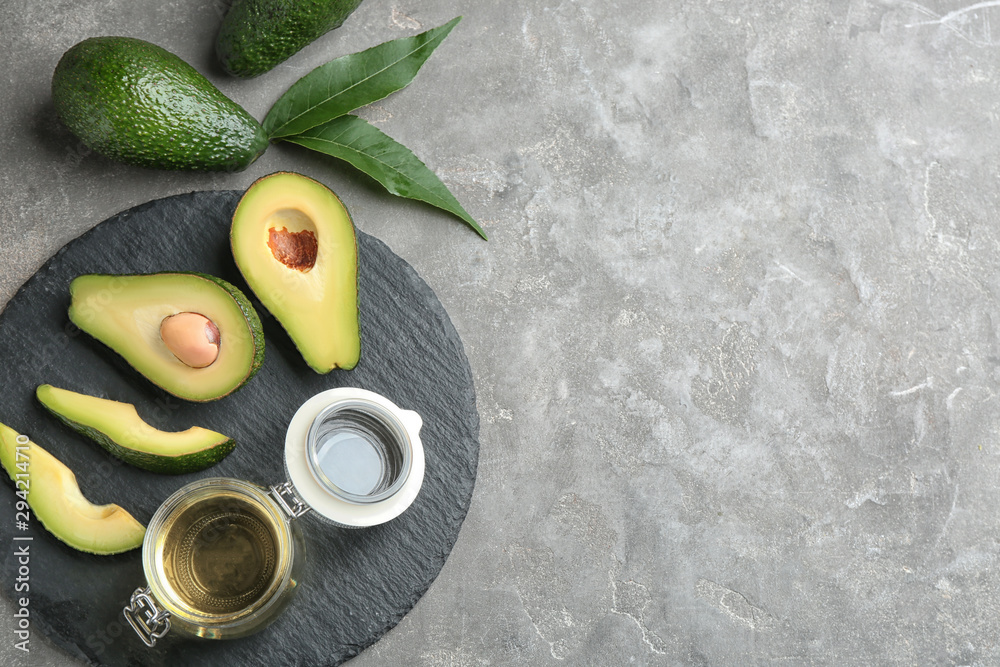 Fototapety, obrazy: Board with jar of natural oil and avocados on grey stone background, flat lay. Space for text