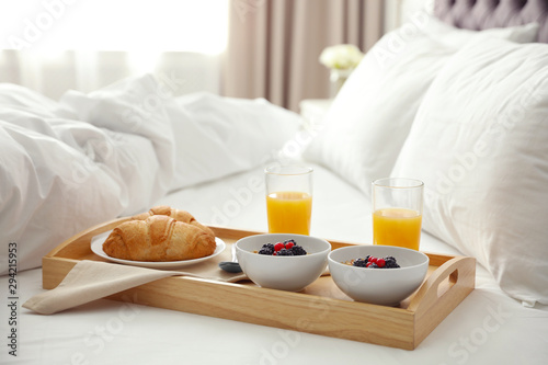 Stampa su Tela Tray with tasty breakfast on bed in light room