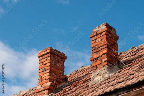Fotografia Two traditional red brick chimneys on an old clay tile roof against a blue sky