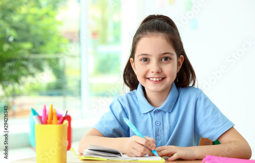 Little girl doing assignment at desk in classroom Canvas Print