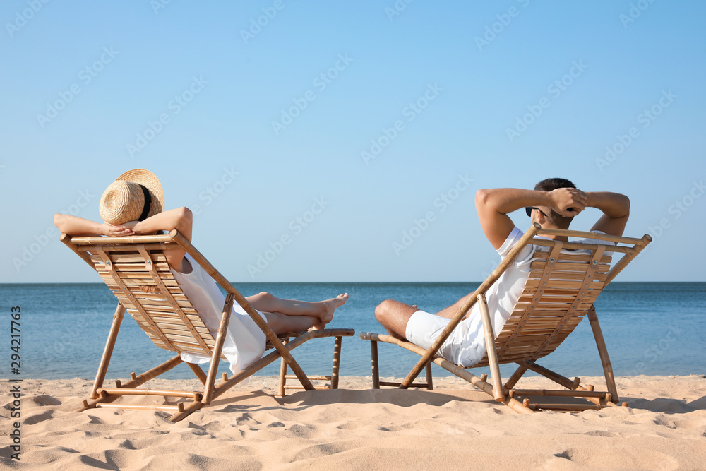 Fototapety, obrazy: Young couple relaxing in deck chairs on beach