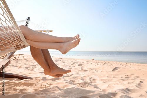 Obraz Young couple relaxing in hammock on beach, closeup - fototapety do salonu