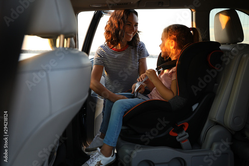 Fototapeta  Woman fastening her daughter with car safety belt