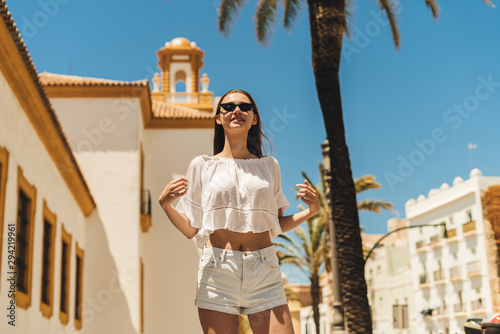 Fotografie, Obraz  Charming young girl with long dark hair in black sunglasses in the white blouse