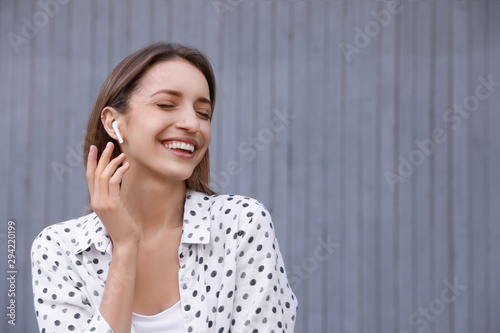Young woman with wireless headphones listening to music near grey wall. Space for text - 294220199