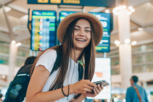 Tanned Girl With Long Dark Hair In A Straw Hat On Her Head And The White T-shirt With  Phone In Her Hands And Backpack On Her Back Is Looking Forward To Her Flight At The Airport To The Plane