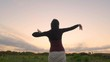 Happy female dance in the summer fields during beautiful sunset