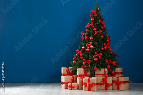 Foto auf Leinwand Baume Decorated Christmas tree and gift boxes near blue wall. Space for text