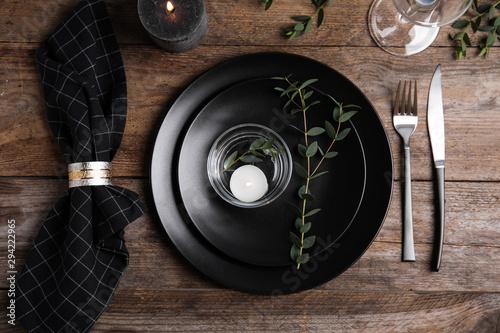Obraz Elegant festive table setting with candle on wooden background, flat lay - fototapety do salonu