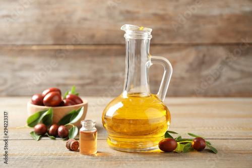 Fototapeta Glass jug with jojoba oil and seeds on wooden table obraz