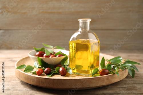 Fototapeta Glass bottle with jojoba oil and seeds on wooden table obraz