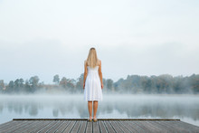 Young Woman In White Dress Standing Alone On Footbridge And Staring At Lake. Mist Over Water. Foggy Air. Chilly Morning. Back View.