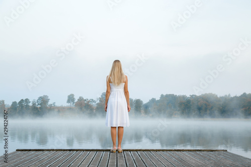 Photo  Young woman in white dress standing alone on footbridge and staring at lake