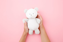 Smiling Small White Teddy Bear In Girl Hands On Pastel Pink Background. Kids Best Friend. Point Of View Shot.