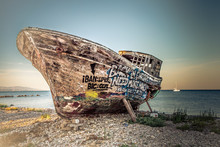 An Old Wooden Fishing Boat Covered In Graffiti On Dry Dock.