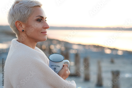 Adult middle-aged blonde woman wrapped herself in a bright plaid on the beach and looks at the sea, selective focus