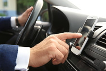 Businessman Using Mobile Phone For Navigation While Driving Car, Closeup