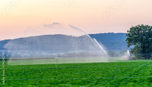 Recess Fitting Green Travelling sprinkler with hose reel irrigation machine spaying water over a farmland during a drought summer