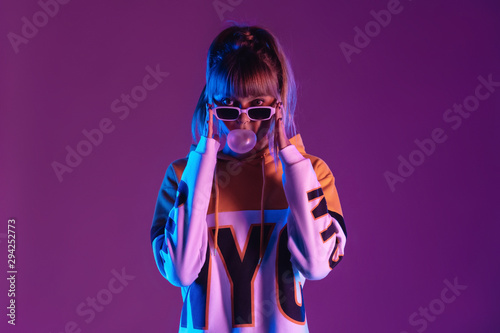 Autocollant pour porte Magasin de musique Pretty young 20s fashion teen girl model wear glasses blowing bubble gum looking at camera standing at purple studio background, igen teenager in trendy stylish night glow 80s 90s concept, portrait