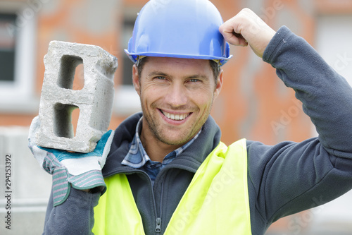 Cuadros en Lienzo confident handsome builder helmet carrying a cement block