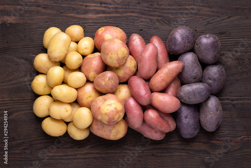 Fotografía  Heap of different types of potatoes on dark wooden rustic table