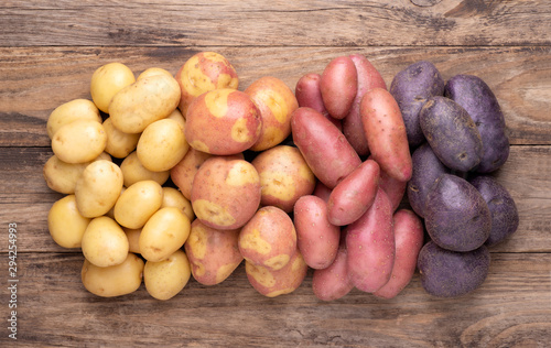 Fotomural Heap of different types of potatoes on wooden rustic table