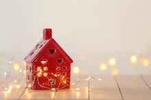 Small House With Glowing Garland On White Table