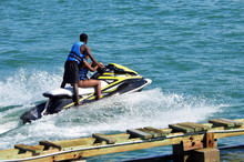 Young Afro American  Couple Riding Tandem On A Black And Yellow Jetski