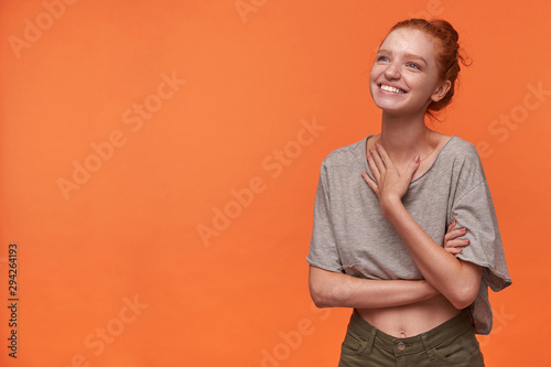 Tela  Attractive young readhead female showing her pleasant emotions over orange backg