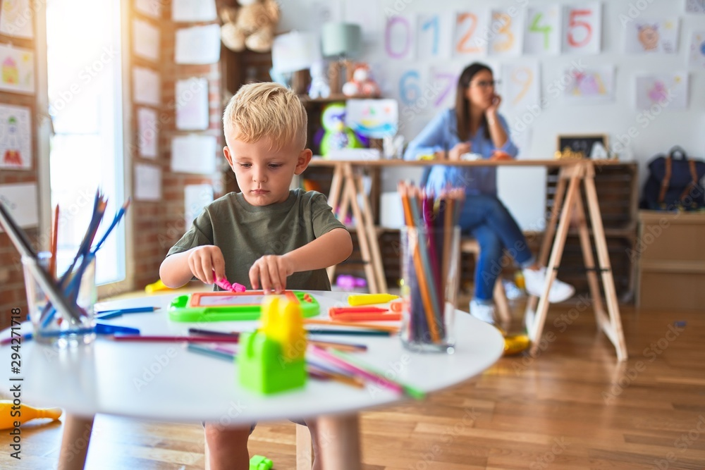Fototapety, obrazy: Young caucasian child playing at playschool with teacher. Mother and son at playroom drawing a draw with color pencils, young woman at the background sitting on desk.