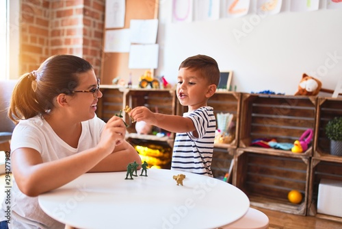 Fototapeta Beautiful teacher and toddler boy playing with figurine army soldiers at kindergarten obraz na płótnie