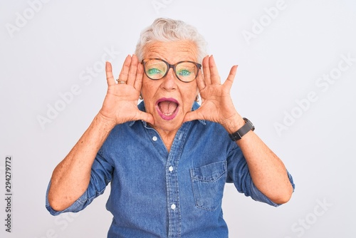 Valokuva  Senior grey-haired woman wearing denim shirt and glasses over isolated white background Smiling cheerful playing peek a boo with hands showing face