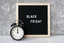 Text Black Friday On Black Letter Board And Alarm Clock On Table Against Grey Stone Background. Concept Black Friday , Season Sales Time