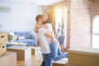 canvas print picture - Young beautiful couple hugging at new home around cardboard boxes