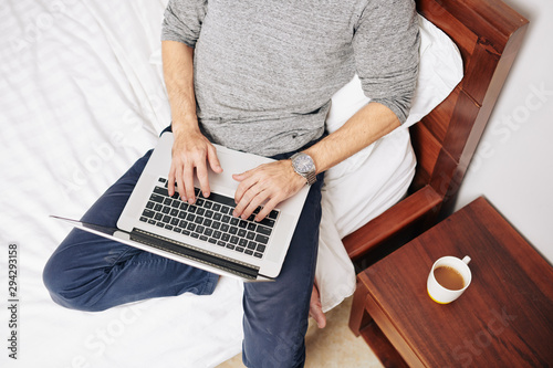 Cuadros en Lienzo  Young man sitting on bed with cup of coffee and working and programming on lapto