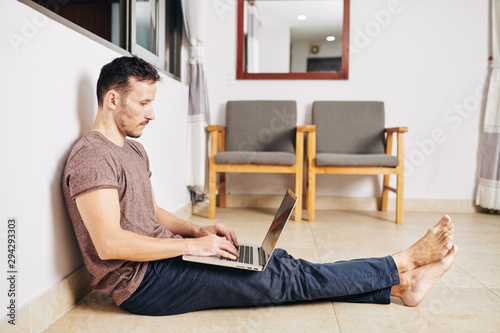 Fotografía  Barefoot young man sitting on the floor under opened window and programming on l