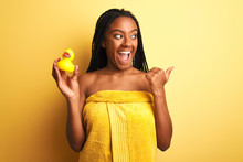 African American Woman Wearing Shower Towel Holding Toy Duck Over Isolated Yellow Background Pointing And Showing With Thumb Up To The Side With Happy Face Smiling