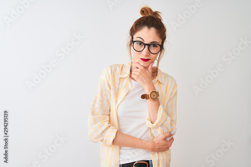 Pinturas sobre lienzo  Redhead woman wearing striped shirt and glasses standing over isolated white background looking confident at the camera smiling with crossed arms and hand raised on chin