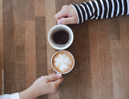 Canvas Prints Cafe Couple hand holding hot coffee cup on wooden table.Business man and woman drinking espresso and latte art menu in the restaurant.Lover in coffee shop.