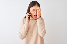 Young Chinese Woman Talking On The Smartphone Over Isolated White Background Yawning Tired Covering Half Face, Eye And Mouth With Hand. Face Hurts In Pain.