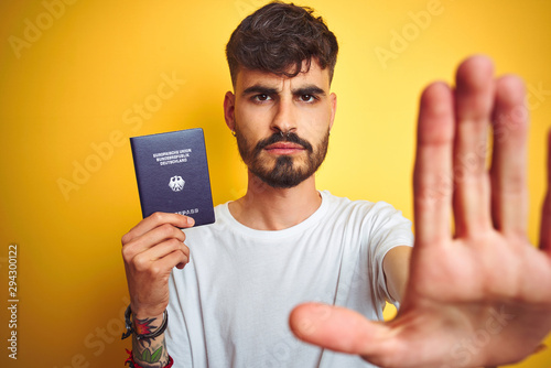 Young man with tattoo wearing German Germany passport over isolated yellow backg Canvas-taulu