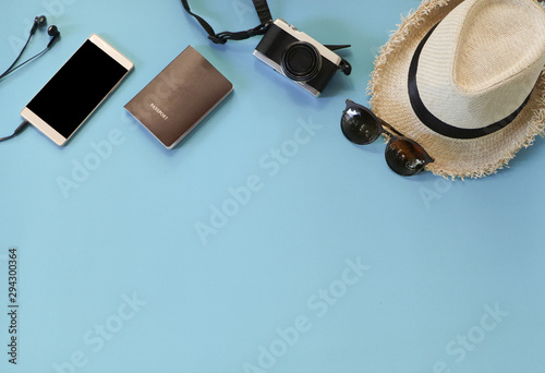 Fototapeta Travel concept . Top view of tourist accessories  on blue  background camera ,hat ,passport, mobile phone,sunglasses. obraz na płótnie