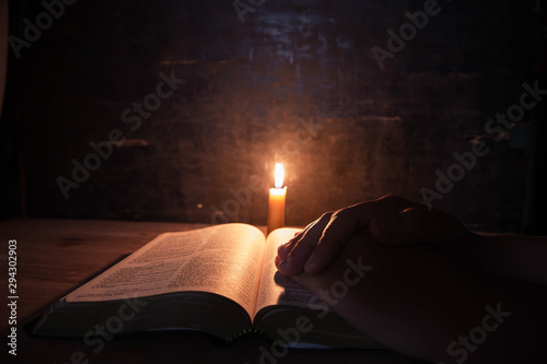 women praying on the Bible in the light candles selective focus. Fototapeta
