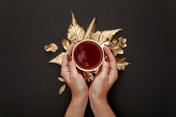 partial view of woman holding tea in mug near golden foliage on black background
